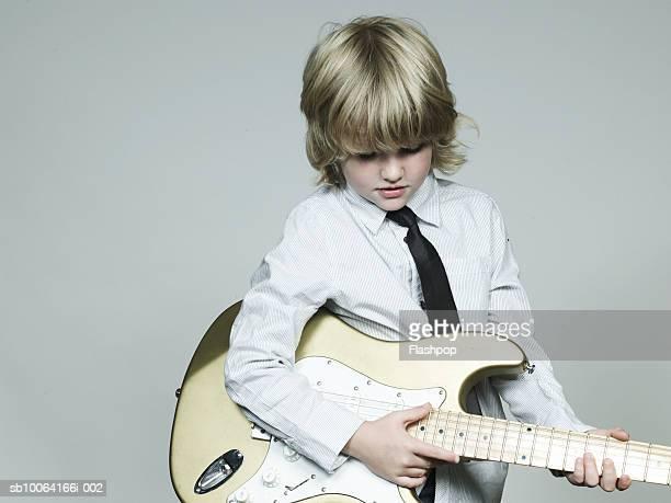 Boy (6-7) playing guitar, close-up