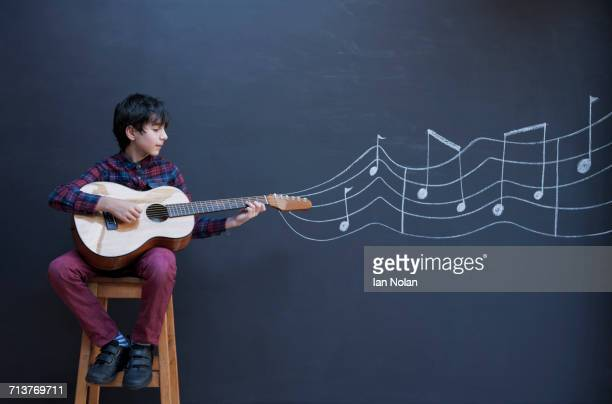 Boy playing guitar in front of chalkboard wall with showing musical notation