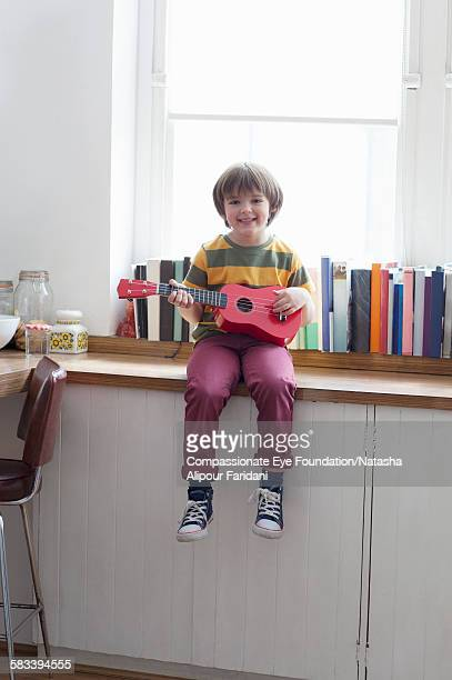 Boy playing guitar in kitchen