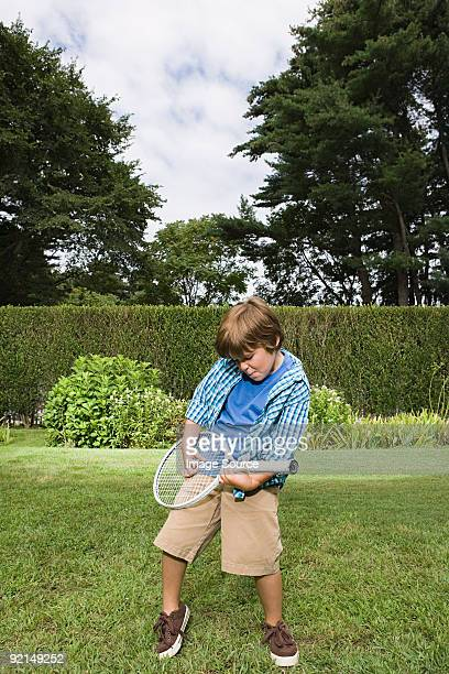 Boy playing guitar on a tennis racket