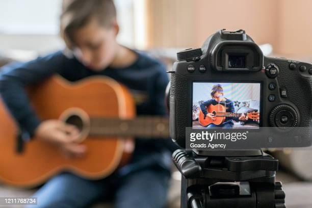 カメラでギターを弾く少年 - 三脚 ストックフォトと画像