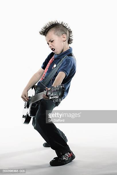 Boy (8-10) playing guitar