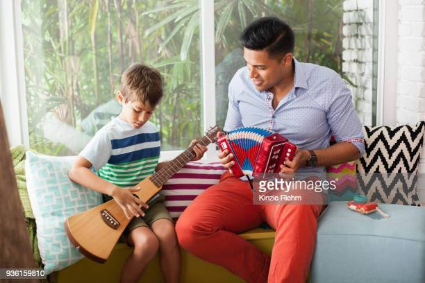 boy playing guitar with music teacher on window seat - accordion instrument stock pictures, royalty-free photos & images