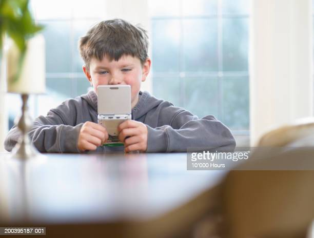 Boy (9-11) playing hand held computer game