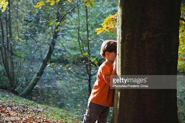 Boy playing hide-and-seek in woods