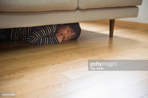 Boy playing hiding in the sofa
