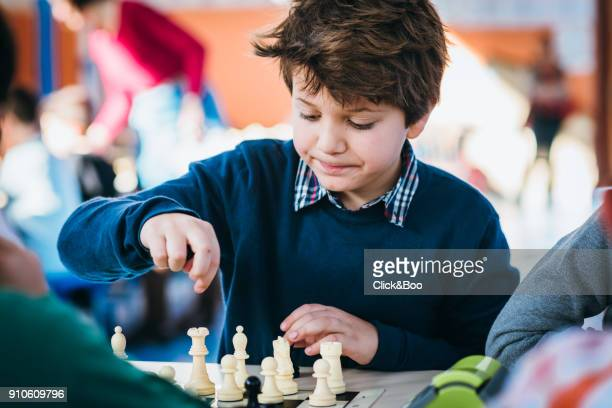 Boy playing in a chess school championship