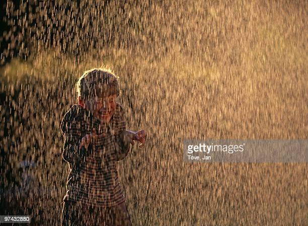 boy playing in a water cascade, sweden. - torrential rain stock pictures, royalty-free photos & images