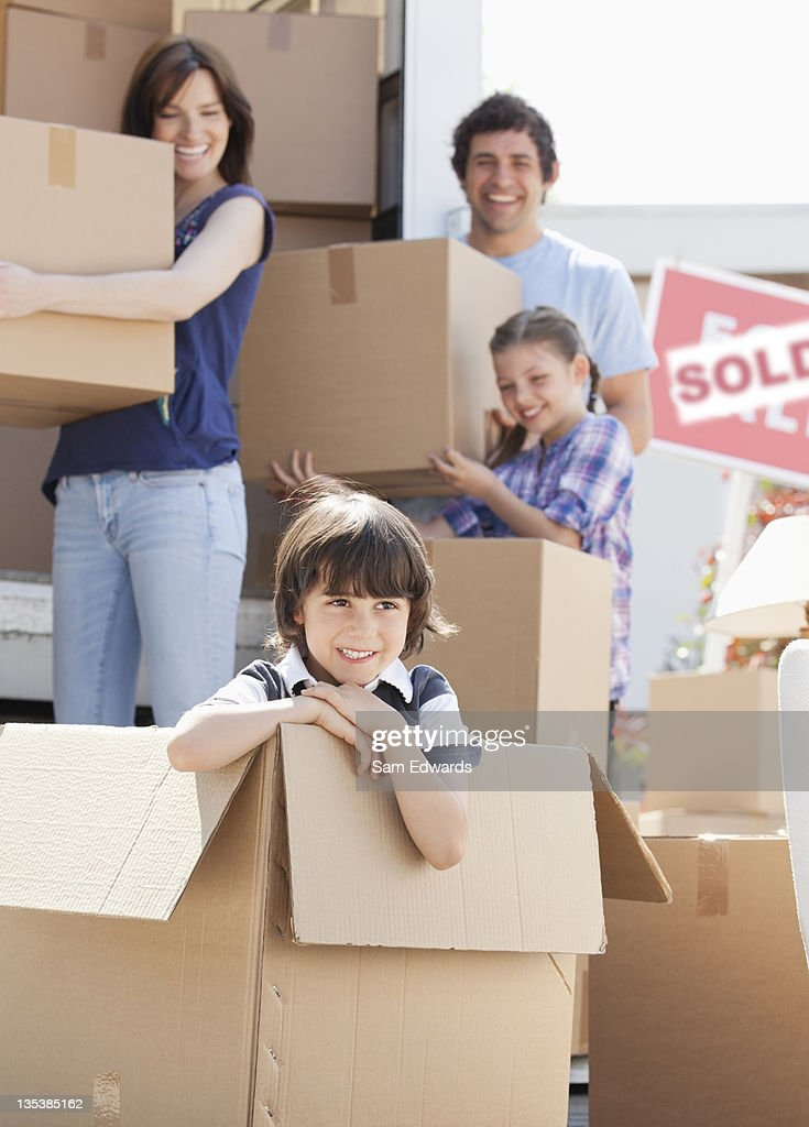 Boy playing in box near moving van : Stock Photo