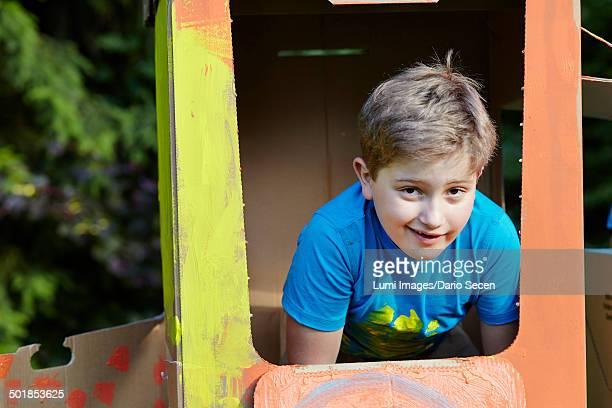Boy playing in cardboard box, Munich, Bavaria, Germany