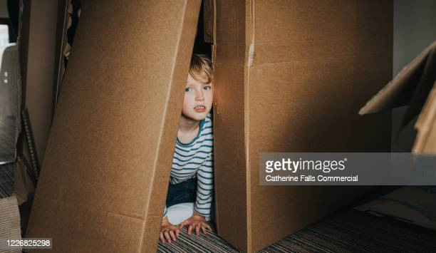 boy playing in cardboard boxes - one boy only stock pictures, royalty-free photos & images