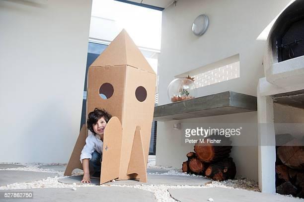Boy (2-3) playing in cardboard toy rocketship
