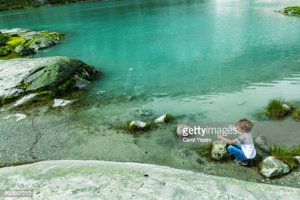 boy playing in edge of water in a lakein  jostedal, nigardsbreen (norway) - close to stock pictures, royalty-free photos & images