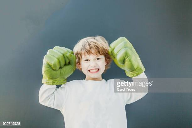boy playing in fake fists