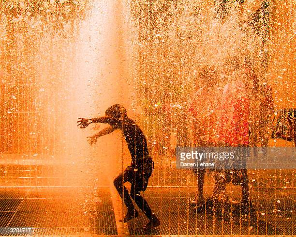 boy playing in fountain - fountain stock pictures, royalty-free photos & images