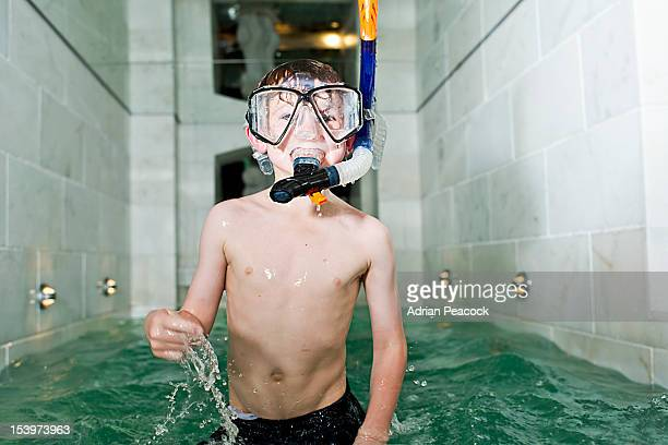 boy playing in indoor pool with snorkel