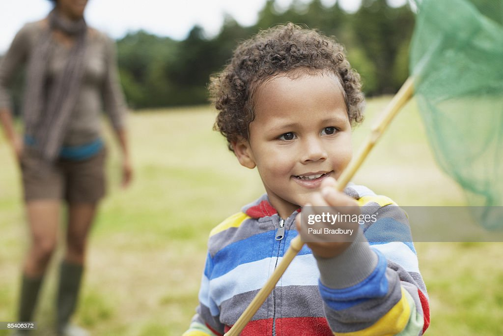 Boy playing in park with butterfly net : Stock Photo