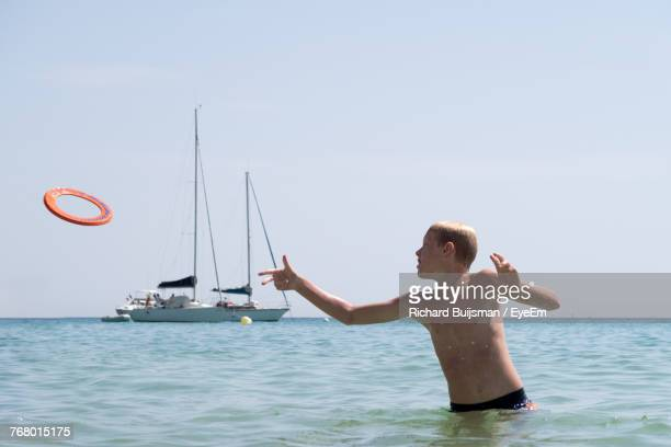 Boy Playing In Sea Against Clear Sky