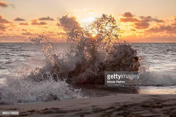 boy playing in splashing waves at sunrise, blowing rocks preserve, jupiter island, florida, usa - jupiter island stock photos and pictures