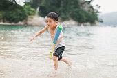 asian boy playing beach