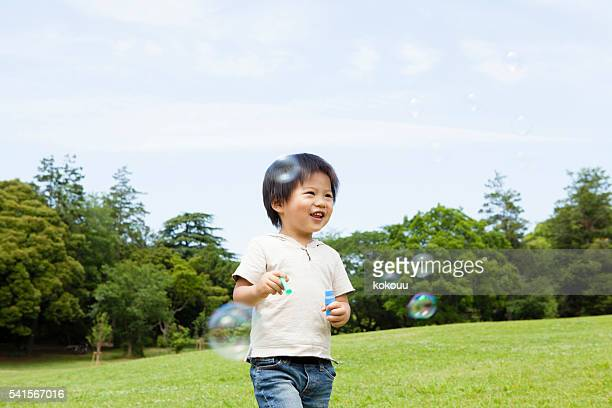 Boy playing in the park a fun in soap bubble