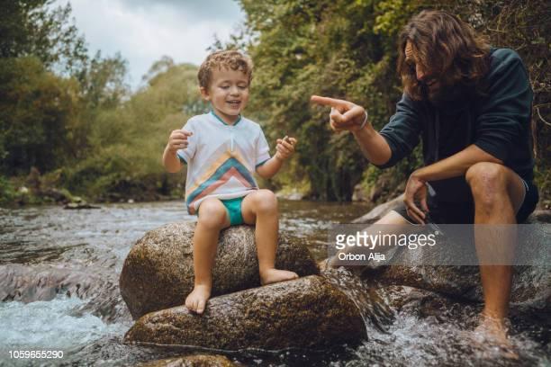 Jungen spielen im Fluss mit seinem Vater