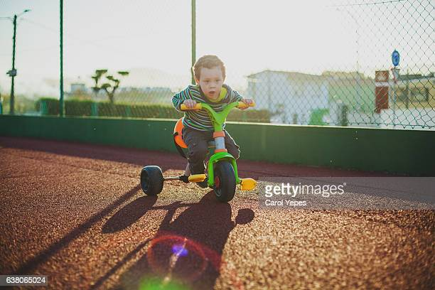 boy playing in trycicle outdoors