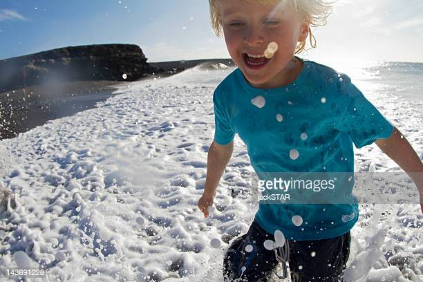 Boy playing in waves on beach