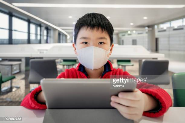 boy playing ipadl with mask at airport - wuhan city stock pictures, royalty-free photos & images