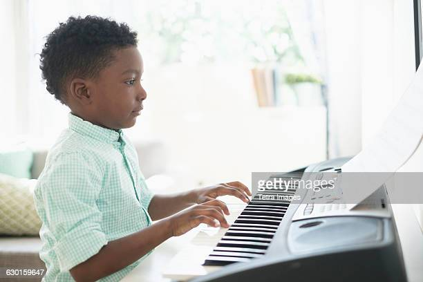 boy (6-7) playing keyboard instrument - keyboard player stock photos and pictures