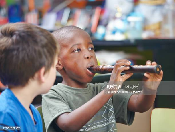 boy playing musical instrument - try scoring stock pictures, royalty-free photos & images