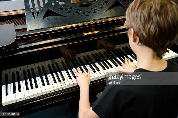 Boy playing old grand piano