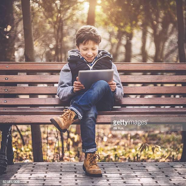 Boy spielen auf einem tablet PC im park