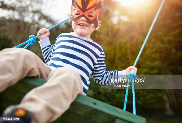 A boy playing on a garden swing wearing a mask
