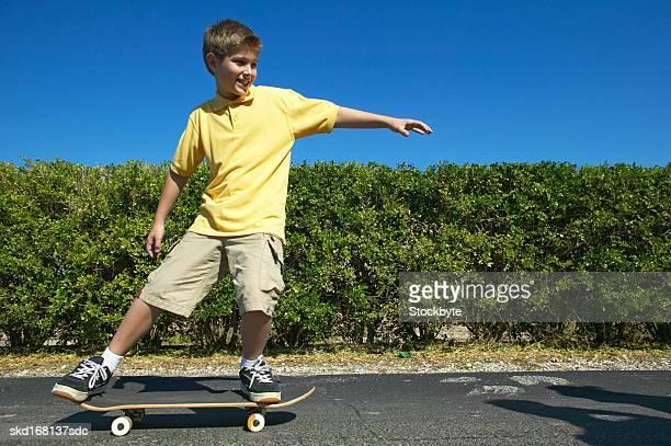 boy (10-11) playing on a skateboard