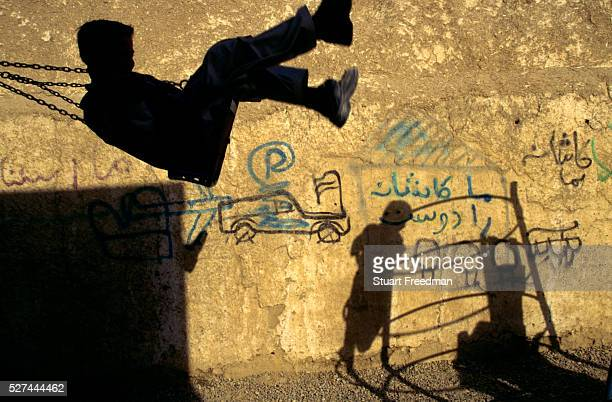 A boy playing on a swing and the shadows of other children on climbing frame in a school yard in MazarIShariff Afghanistan