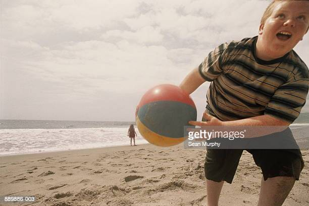 boy (10-13) playing on beach, with ball - chubby boy - fotografias e filmes do acervo