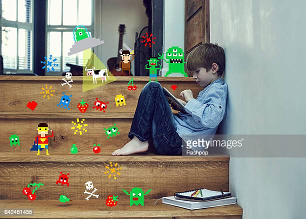 Boy playing on digital tablet with game symbols