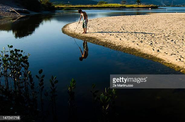 Boy playing on edge of lake