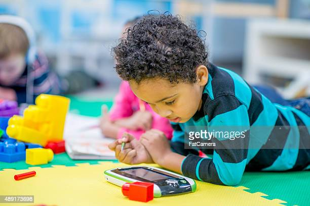 Boy Playing on Electronic Tablet