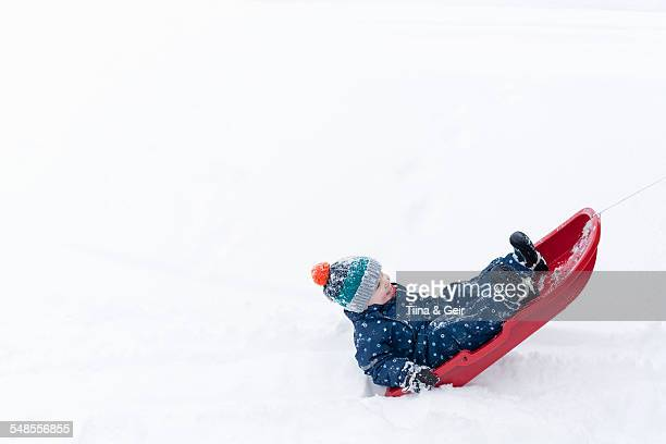 boy playing on his toboggan in the snow - tobogganing ストックフォトと画像