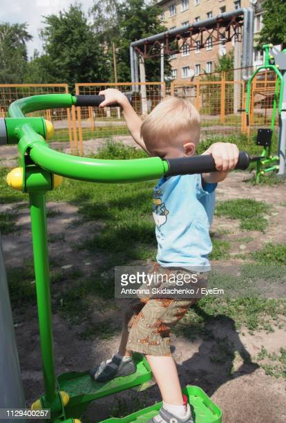 Boy Playing On Outdoor Play Equipment In Playground