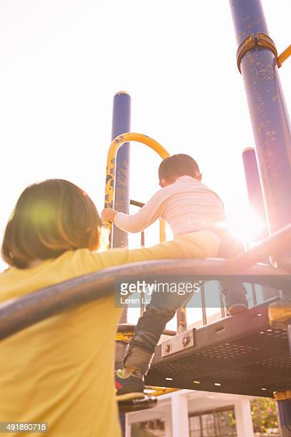 Boy playing on playground with mother.