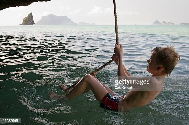 boy playing on rope over water - zwembroek stockfoto's en -beelden