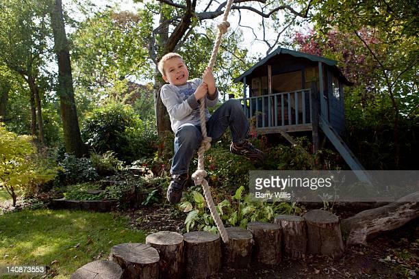 Junge spielt auf Seilschaukel im Garten