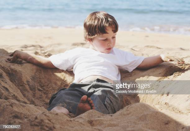 Boy Playing On Sand At Beach