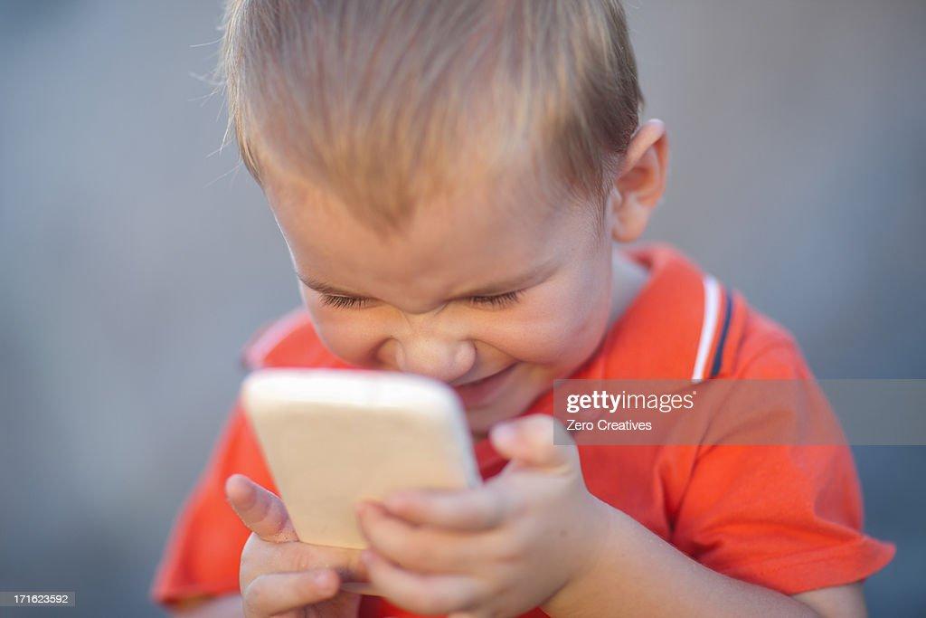 Boy playing on smartphone : Stock Photo