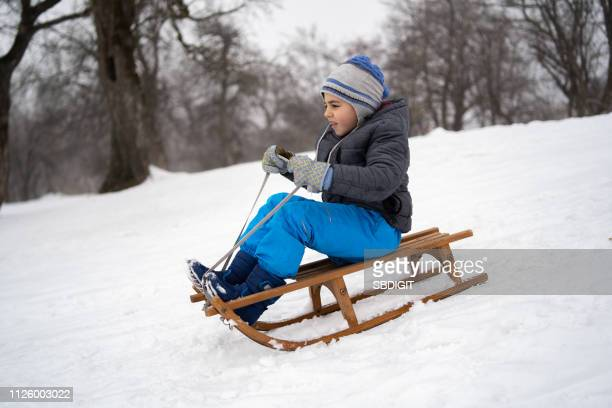 boy playing on snow - sleigh stock photos and pictures
