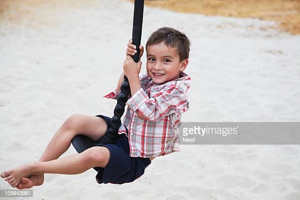 boy playing on swing at playground - schommelen bungelen stockfoto's en -beelden