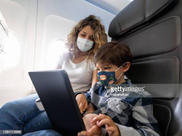 boy playing on tablet during a commercial flight while traveling with his mother wearing a facemask - biosecurity stock pictures, royalty-free photos & images